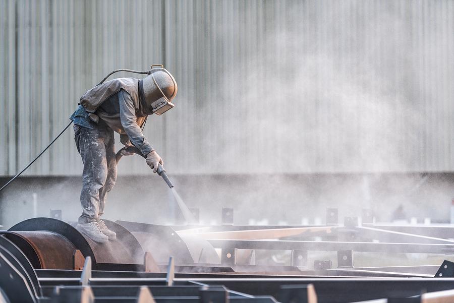 Worker wearing PPE for abrasive blast